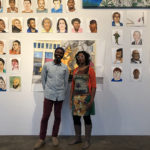 """Kemi and Rudy pose in front of """"Everything in the Universe is My Brother"""" at Smack Mellon. Photo Credit: Eric Booker"""